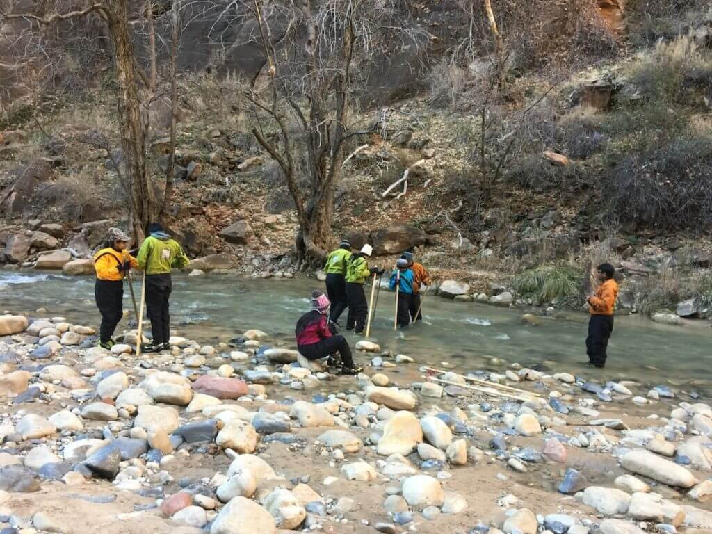 Hikers preparing for walks through the water in Zion National Park